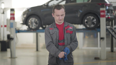 Middle shot of positive young Caucasian auto mechanic taking off protective Live Action