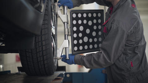 Close-up of male Caucasian auto mechanic coming to car, adjusting equipment on Live Action