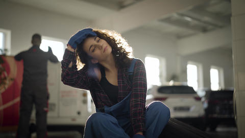 Portrait of young Caucasian female auto mechanic sitting in sunrays in auto Live Action