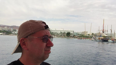 Eilat, Israel - October 24, 2019: Tourist looks into the distance at passing Live Action