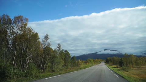 Driving a car on asphalt road in Norway with mountains and clouds in autumn Live Action