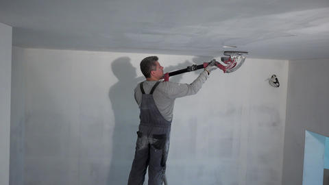 Construction worker smoothing wall surface with sanding machine Live Action