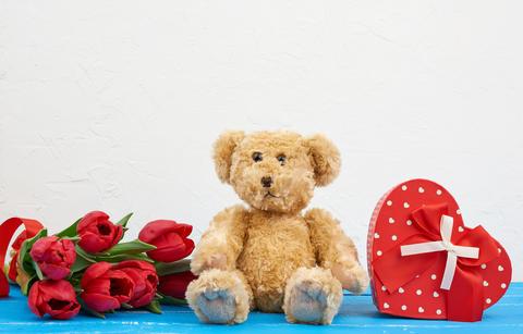 cute brown teddy bear sits on a blue wooden background, bouquet Fotografía