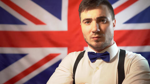 Portrait of a serious British man in a bow tie and white shirt on the background Live Action