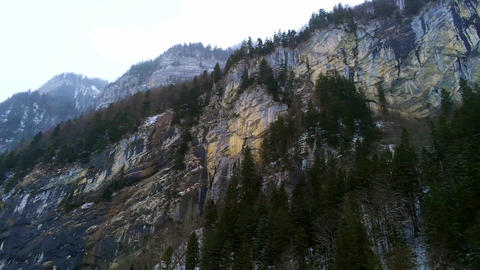 Amazing steep cliffs in the Swiss Alps on a cold winters`s day - aerial drone Live Action