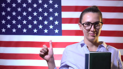 Student girl in glasses with a textbook shows thumb up on the background of the Live Action