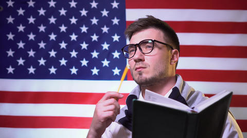 A pretty student in glasses with books in a shirt stands in front of the flag Live Action