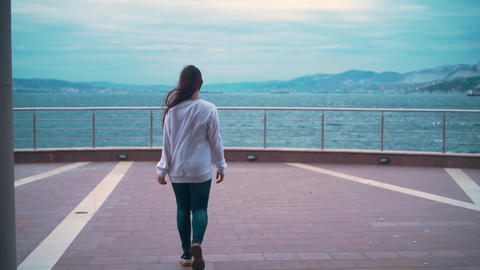 A girl is walking along the observation deck against the backdrop of a stormy Live Action