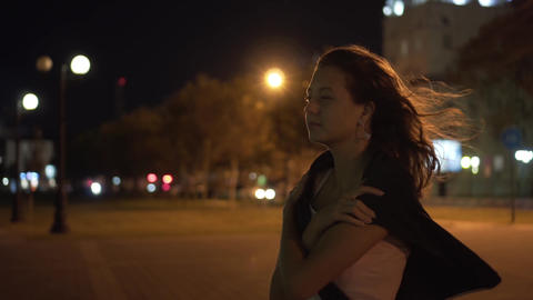 Beautiful girl at night in the city, the wind blows her hair. Elegance of a girl Live Action
