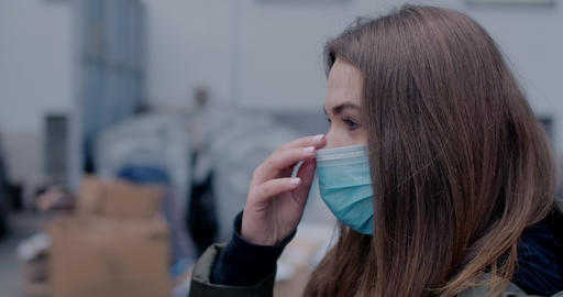 Side view close-up of brunette woman adjusting protective mask. Young lady Live Action