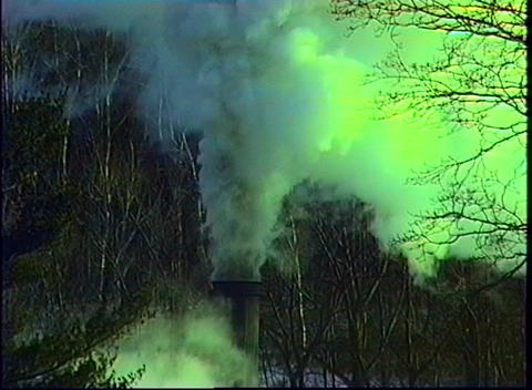 Green smoke billows up from a smokestack, polluting a... Stock Video Footage