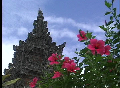 A worms-eye view of a Hindu temple, with lovely pink flowers in the foreground, in Bali Indonesia Footage