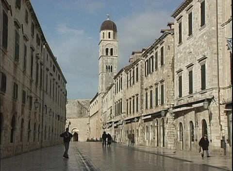 A medium shot of people walking down a narrow street in Dubrovnik, Croatia with a church in the back Footage
