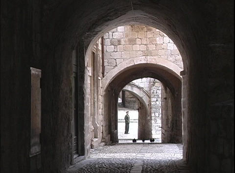 A man stands in a courtyard at the end of several archways in the city of Dubrovnik Footage