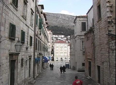 A medium shot of people walking down the narrow streets of Dubrovnik, Croatia Footage