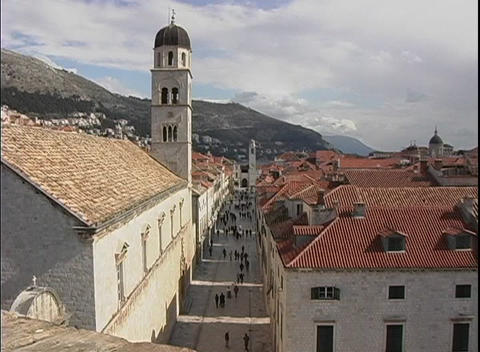 Zoom-out from of a steeple of a church, past rooftops of buildings to the hills and sea surrounding Footage