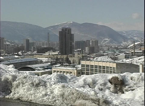An establishing-shot overlooking the snow covered city of Sarajevo in Bosnia from a plowed road Footage