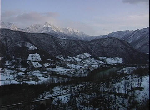 Pan-right over Bosnia's snow covered valley with snowy, rugged, mountains in the background Footage