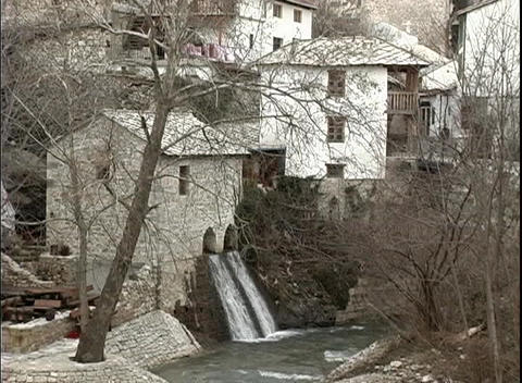 Medium-shot of two man-made waterfalls flowing into a canal in a town in Bosnia Footage