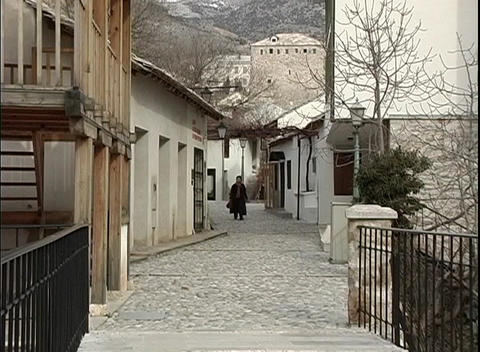 A medium-shot of a person strolling along an alley in Bosnia Live Action