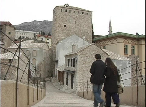A couple walks down a flight of stairs, toward old stone... Stock Video Footage