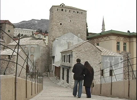 A couple walks down a flight of stairs, toward old stone buildings in Bosnia Footage