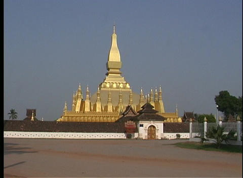 Motorcyclists make their way past the majestic golden Pha That Luang Temple in Vientiane, Laos Footage