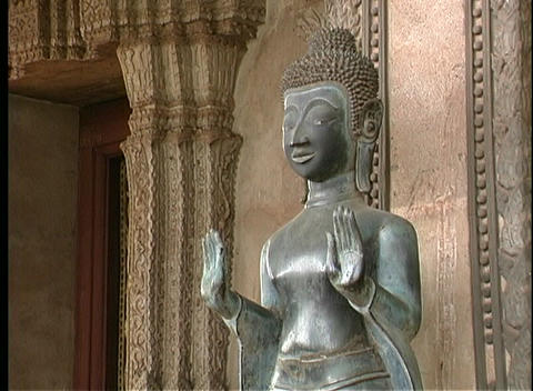 A close-up of a silver statue near the entrance of a Buddhist temple in Laos Live Action