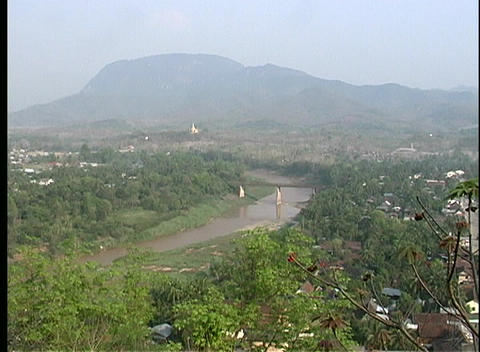 A pan-left, bird's-eye view of a town nestled in a lush green valley Footage
