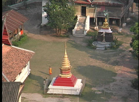 Buddhist Monks walk around a courtyard in an Asian community, in this birds-eye view Footage