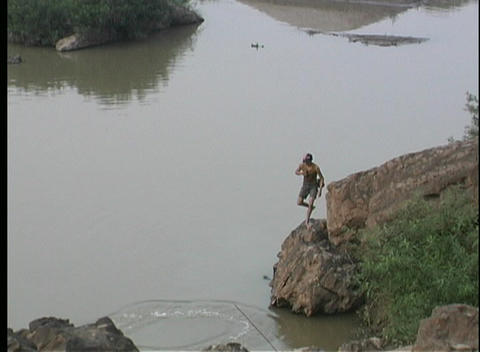 A birds-eye view of a fisherman casting his net on the water in Asia Footage