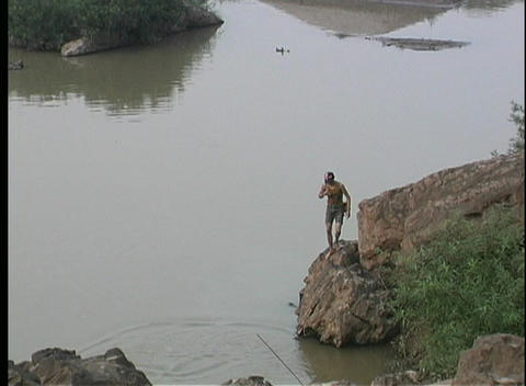 A birds-eye view of a fisherman casting his net on the... Stock Video Footage