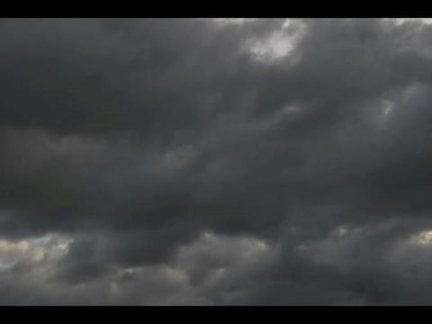 Time-lapse of dark clouds moving across a blue sky Footage