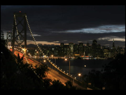 Time-lapse of a darkening sky behind a busy city suspension bridge Footage