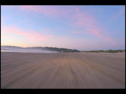Moving time-lapse along a beach under a colorful sky Footage