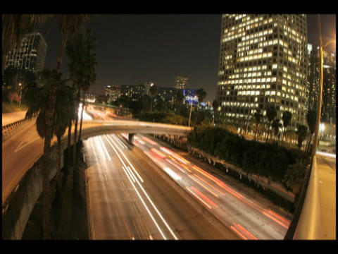 Time-lapse of city traffic on highways and overpasses at night Footage