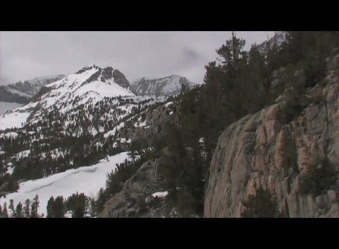 Snowy, rugged mountains rise behind rocky bluffs in a... Stock Video Footage