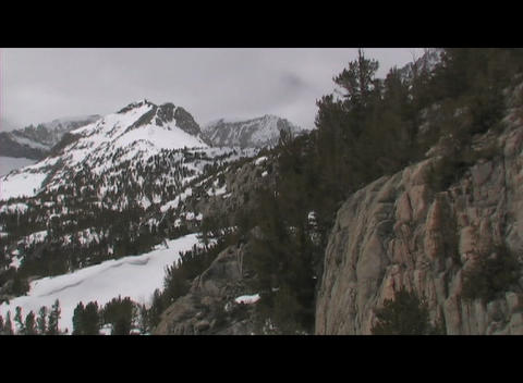 Snowy, rugged mountains rise behind rocky bluffs in a wilderness area Footage