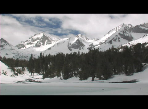 Rugged mountains rise behind a frozen lake in a wintry wilderness area Footage