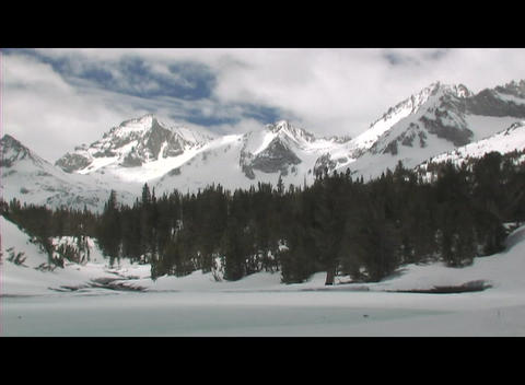 Rugged mountains rise behind a frozen lake in a wintry... Stock Video Footage