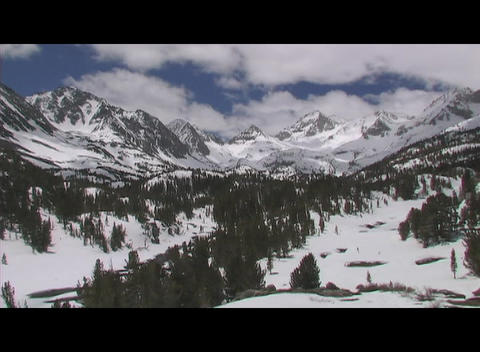 Fluffy white clouds pass in a blue sky above a wintry wilderness landscape Footage