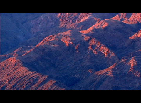 Orange and red colors glow on one side of a rugged... Stock Video Footage
