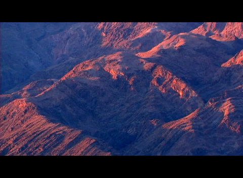 Orange and red colors glow on one side of a rugged mountain range while the other side is dark Footage