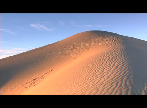 Golden light shines on one side of a sand dune Footage