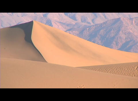 Rugged mountains rise behind a smooth golden sand dune Footage