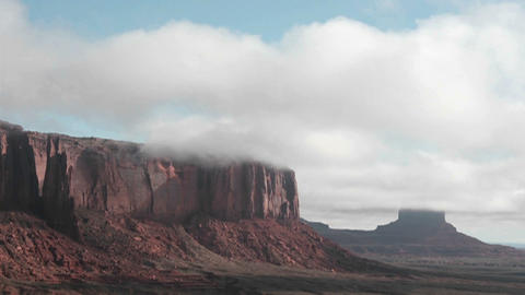 Clouds stream over rock formations in Monument Valley, Utah Stock Video Footage