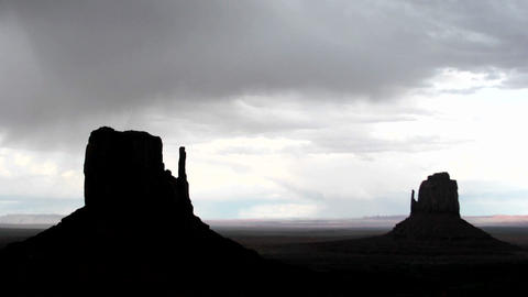 Ominous storm clouds move quickly over Mitten Buttes in Monument Valley, Utah Footage