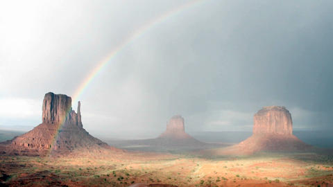 A rainbow fades in the sunlight following a storm over... Stock Video Footage