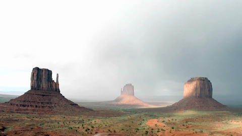 A rainbow fades in the sunlight following a storm over Monument Valley, Utah Footage