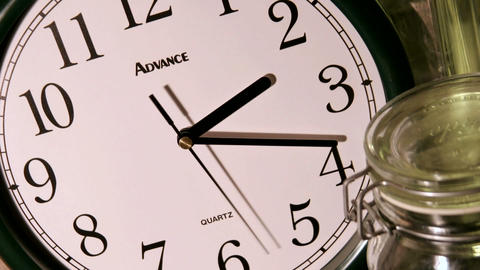 A second hand moves counterclockwise, as minute and hour hands rapidly mark time on a clock face Footage